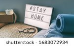 Small photo of Coronavirus Yoga at home sign lightbox with text hashtag #STAYHOME glowing in light with exercise mat, cork blocks, strap meditation pillows. COVID-19 banner to promote self isolation staying at home.