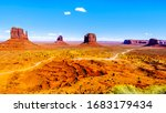 The gravel road winding around Mitten Buttes, Merrick Butte and other large sandstone formations in Monument Valley Navajo Tribal Park in southern Utah, United States