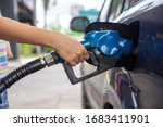 Small photo of Blue car at gas station filled with fuel. Closeup woman hand pumping gasoline fuel in car at gas station. woman refuel car petrol pump filling gas at gas pump.