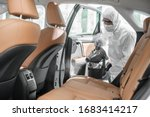 Small photo of Disinfectant worker character in protective mask and suit sprays bacteria or virus in a car.
