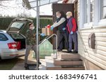 Small photo of coronavirus pandemic. Epidemic. A volunteer / soldier brought food for senior citizens. On the steps, a volunteer in a medical mask and gloves passes a bag of products to an elderly couple in masks