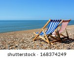 Two Deckchairs On A Pebbled...