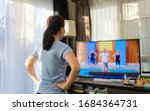 Small photo of Video streaming Stay home.home fitness workout class live streaming online.Asian woman doing strength training cardio aerobic dance exercises watching videos on a smart tv in the living room at home.