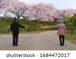 Small photo of Social distancing. A good example of social distancing to avoid the spread of coronavirus (COVID-19). Two people (a man and a woman) stand apart holding two umbrellas.