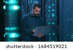 Small photo of Caucasian IT professional admin using laptop computer doing data transfer operation with rack server cabinets in digital room of data center. Cyber security.