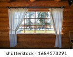Small photo of Log cabin window. Looking through the window from inside. Nature behind window glass. Window frame and curtain. Triangle. Timber construction. Wooden, log hut. Warm wooden shack. Sunny weather