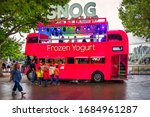 Small photo of London, U.K, Aug 2019, Snog pink bus on the Southbank selling ice cream to a family