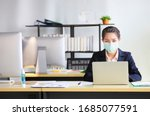 Small photo of Female employee wearing medical facial mask working alone as of social distancing policy in the business office during new normal change after coronavirus or post covid-19 outbreak pandemic situation