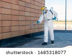 Small photo of Man wearing an NBC personal protective equipment (ppe) suit, gloves, mask, and face shield, cleaning the streets with a backpack of pressurized spray disinfectant water to remove covid-19 coronavirus.