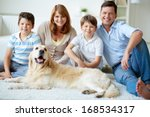 Stock photo portrait of happy family with their pet having rest at home 168534317