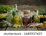 Small photo of Bottles of tincture or infusion of healthy medicinal herbs and healing plants on wooden table. Herbal medicine.