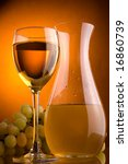 a glass and jug of white wine and grape - stock photo