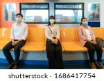 Small photo of Three Asian people wearing mask sitting in subway distance for one seat from other people keep distance protect from COVID-19 viruses and people social distancing for infection risk