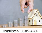 Small photo of Closer to the hand of a businessman who is stacking coins on top of each other, model houses are close to each other. Real estate investment, saving for buying for housing or speculation concept