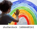 Small photo of Chase the rainbow. child at home draws a rainbow on the window. Flash mob society community on self-isolation quarantine pandemic coronavirus. Children create artist paints creativity vacation