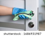 Small photo of Sterile cleaning of door handles during a coronavirus pandemic. Alcohol-based cleaner, gloves and a napkin.
