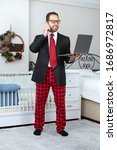 Small photo of Young business man work from home during Coronavirus pandemic quarantine. Handsome man in suit and pajama pant working from home office. Freelance work. Working online.