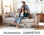 Small photo of Portrait of smiling bearded father standing near couch with sitting happy wife and little children. Joyful affectionate family of four posing for photo, looking at camera, good relations concept.