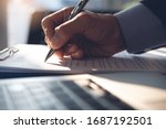Small photo of Businessman, executive manager hand filling paper business document, signing contract, partnership agreement and working on laptop computer on desk in modern office, close up