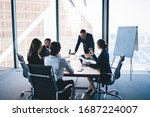 Small photo of Group of coworkers in formal wear sitting at table in conference room and arguing about project of company development during meeting