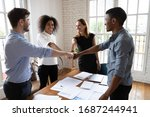 Small photo of Multi-ethnic young happy associates putting fists together forming a circle, gesture of alliance, membership and respect, showing amity and support, having fun in office boardroom start group meeting