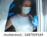 Small photo of COVID-19 Pandemic Coronavirus Mask Woman nurse hospital or home isolation auto quarantine for virus SARS-CoV-2. Girl voluntary isolation with surgical mask looking outside. Disease 2019.