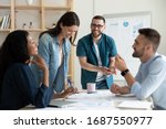 Small photo of Smiling diverse colleagues gather in boardroom brainstorm discuss financial statistics together, happy multiracial coworkers have fun cooperating working together at office meeting, teamwork concept