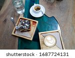 Two cups of coffee with latte art on design wooden background with fresh baked almond pastry bun and chocolate. Beautiful brunch in coffee shop on design epoxy blue river table.