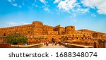 Small photo of Agra Fort - Historic red sandstone fort of medieval India on bright sunny day. Agra Fort is a UNESCO World Heritage site in the city of Uttar Pradesh India. Tourists at entrance to Agra Fort. - Image