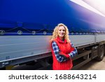 Portrait of female trucker with crossed arm proudly standing by her truck vehicle ready for transportation service. - stock photo