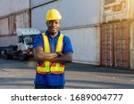 African American transportation factory truck driver with yellow helmet and safety vest is standing and smiling by action arms crossed in front of lorry at container yard of port on evening. - stock photo
