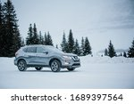 Small photo of Banff, Alberta / Canada- December 14, 2018: Grey Nissan Rogue parked amidst snowy winter scene. Side view