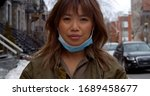 woman partially wears face mask ... | Shutterstock . vector #1689458677