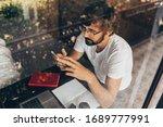 handsome man with beard using... | Shutterstock . vector #1689777991