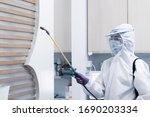 Small photo of worker from decontamination services wearing personal protective equipment or ppe including white suit mask and face shield spraying disinfectant to cleaning coronavirus infection