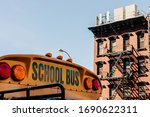 Detail of the text school bus on the front of a bus and in the background a typical new york city building.