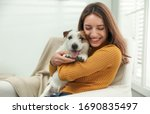 Small photo of Young woman with her cute Jack Russell Terrier at home. Lovely pet