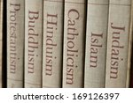 Book spines listing major world religions - Judaism, Islam, Catholicism, Hinduism, Buddhism and Protestantism. The focus is on the word, Catholicism.