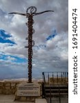 Small photo of The Brazen Serpent on Mount Nebo, next to Moses Memorial Basilica, Kingdom of Jordan, scenery view with the Promised Lands, Israel. Cloudy winter afternoon sky.