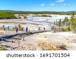 Unrecognizable visitors walking on the Porcelain Basin boardwalk trail surrounded by geothermal pools inside Norris Geyser Basin of Yellowstone National Park, Wyoming, USA.