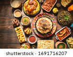 """Small photo of Arabic Cuisine: Middle Eastern traditional lunch. It;s also Ramadan """"Iftar"""" . The Meal eaten by Muslims after sunset during Ramadan. Assorted of Egyptian oriental dishes. Top view with copy space."""