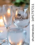 Small photo of Braselton, GA / USA - October 26th 2019: Close up of wine glasses at Chateau Elan winery vineyard on a wedding day at a reception in rustic room with wooden barrels.