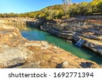 Small photo of Canyon Lake Gorge formed in 2002 after many inches of rain fell and washed out the land. Just outside of New Branfels, Texas the gorge has uncovered dinosaur tracks, fossils, interesting geologically