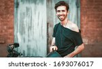 Cheerful Motorbiker Shows V Sign Toothy Smiling, Bearded Caucasian Man Smiles Looking At Camera While Standing With Motobike On Brick Wall And Garage Door Background, Copy Space On Left Side