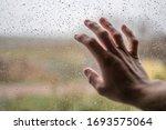 Man Touches Rain Soaked Window...