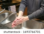 young woman washing her hands... | Shutterstock . vector #1693766701