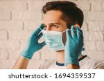 Small photo of Confident young surgeon doctor in latex protective gloves wearing medical mask on face. Man professional medic in medical gloves put on protective face mask. Personal protection. Coronavirus COVID-19