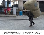 Small photo of Darjeeling, India - March 04 2020: Darjeeling Mall Porters are an indispensable part of hill's life and they ferry imdit every item, be it rice sacks, furniture or other heavy goods.