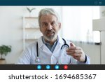 Small photo of Ask general practitioner online, video call consultation, patient and doctor talk concept. Head shot of mature male therapist share information provide support, laptop screen view, videoconference app