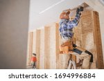 Caucasian Construction Contractor Worker Attaching Drywall to a House Ceiling. Construction Industry Theme. - stock photo